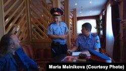 Казахстанские полицейские опрашивают журналиста Александра Гороховского незадолго до того, как его подвергнут штрафу по обвинению в предполагаемом нарушении законодательства о трудовой деятельности. Уральск, 15 сентября 2018 года.
