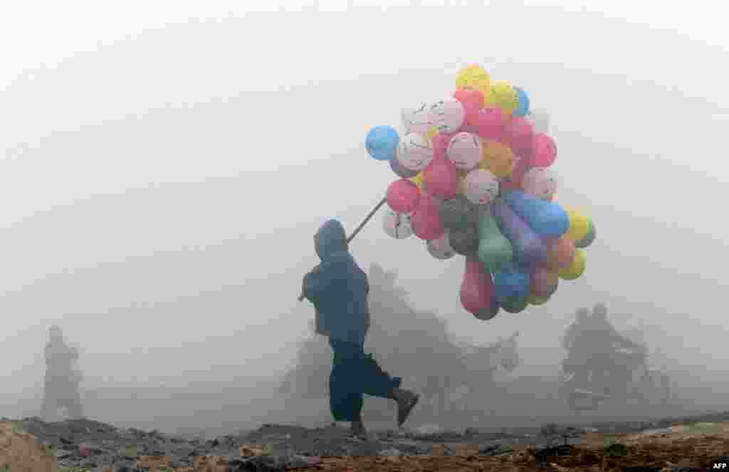 A balloon vendor sells his wares on a cold and foggy morning in Lahore, Pakistan. (AFP/Arif Ali)