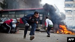 Supporters of Egypt's deposed President Muhammad Morsi run for cover from tear gas fired by riot police during clashes in the northeastern part of Cairo's Nasr City district on January 3.