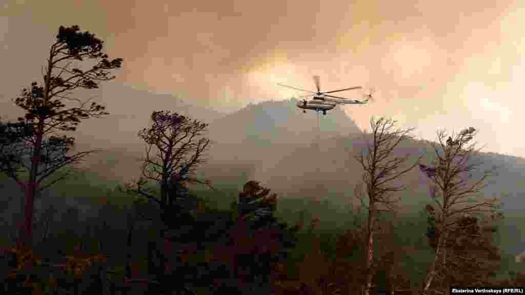 File image of a helicopter fighting a blaze near Lake Baikal. According to a recent scientific study, fires are the reason Siberia is steadily losing its conifer trees. The more adaptable trees that replace the charred conifers dry out the landscape, further increasing the risk of summer wildfires.