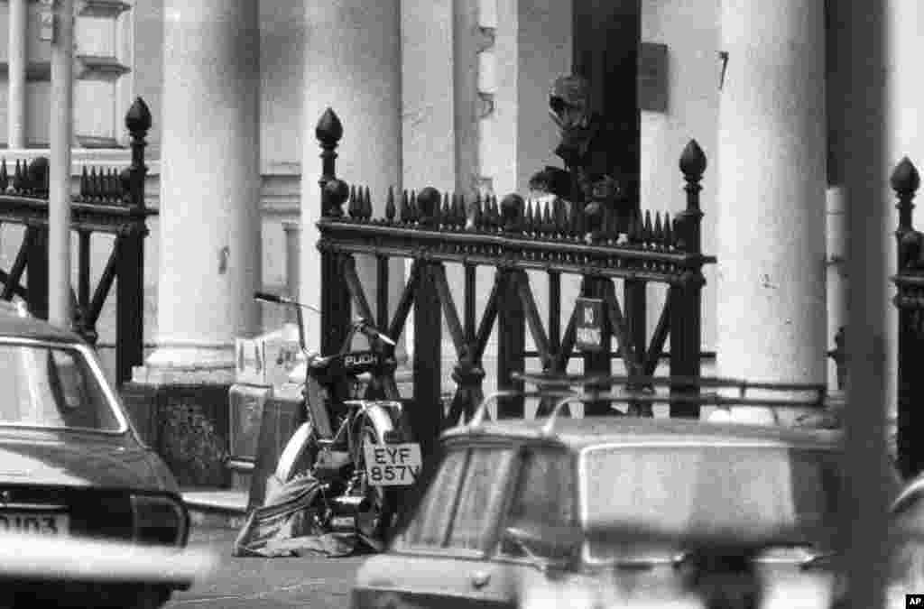 A hooded man appears at the door of the Iranian Embassy in London on May 2, 1980, with what appears to be a gun in his left hand. The hostage takers had their demands aired on the BBC. The broadcast was arranged after negotiations with police. The release of five hostages was secured in exchange.