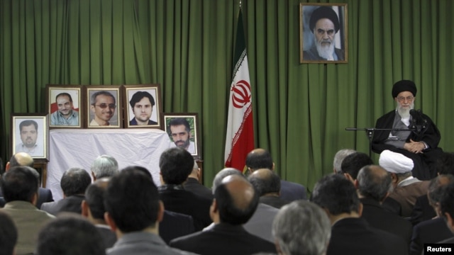 Iranian Supreme Leader Ayatollah Ali Khamenei (right) attends a meeting in February in Tehran with Iranian nuclear scientists and managers as portraits of recently slain Iranian scientists are displayed.