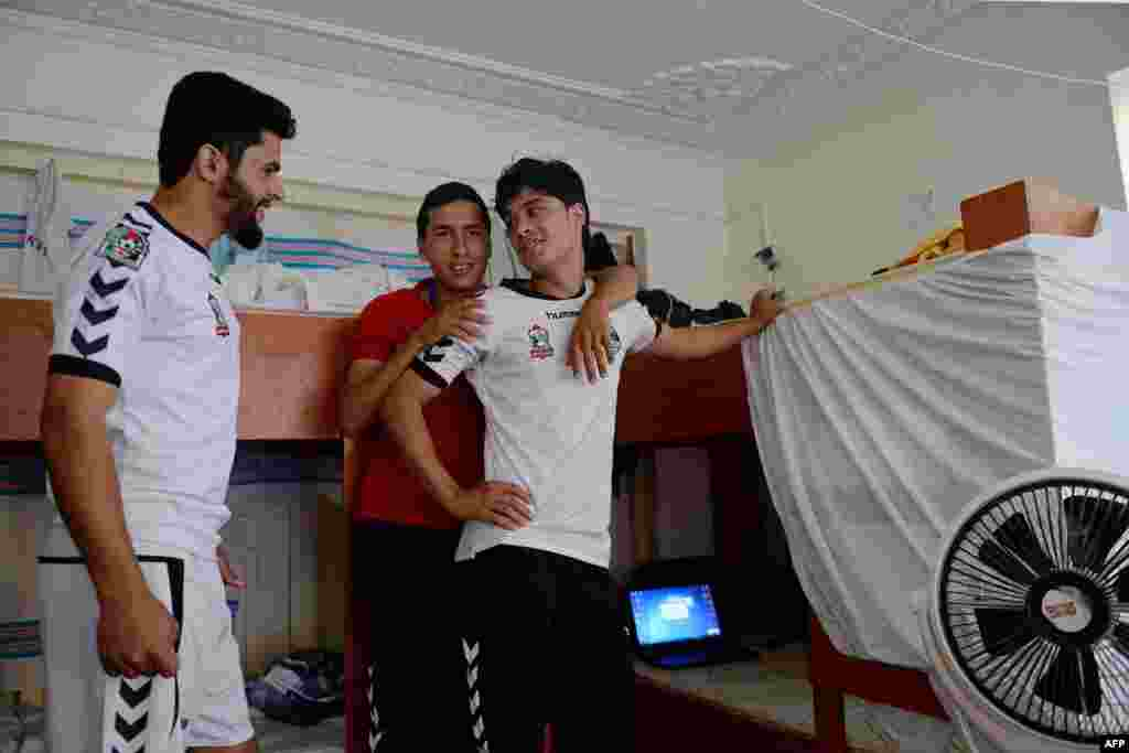 Afghan football player Emal Mangal (left), 19, talks with other players in his dorm room in Kabul on September 2.
