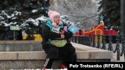 Женщина с флажком Казахстана на площади возле памятника Шокану Уалиханову. Алматы, 14 ноября 2020 года.