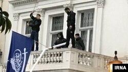 Четверо мужчин на балконе посольства Ирана в Лондоне размахивают флагами, устраивая протест против политики Тегерана. 9 марта 2018 года