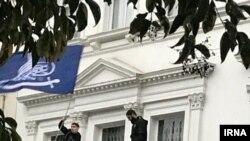 Четверо мужчин на балконе посольства Ирана в Лондоне размахивают флагами, устраивая протест против политики Тегерана. 9 марта 2018 года.