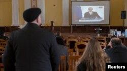 Люди в здании мэрии Киева сидят перед экраном, по которому транслируют выступление президента России Владимира Путина. 18 марта 2014 года.