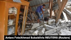 Indonesia, Lombok Timur, A villager walks through the ruins of a collapsed house during a search for the equipment of Malaysian tourists