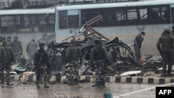 Indian security forces inspect the remains of a vehicle following an bomb attack in Kashmir on February 14.