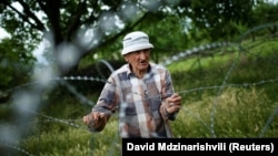 Villager Davit Vanishvili stands near the barbed-wire de facto border separating Georgian territory from Russia-backed breakaway land.
