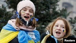 Киевдин Эркиндик аянтындагы европачыл демонстрант кыздар ырдап жатат. 15-декабрь, 2013.