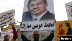 Пратэстоўца з каляжом з партрэтаў былога прэзыдэнта Хосьні Мубарака і цяперашняга Мухамада Мурсі