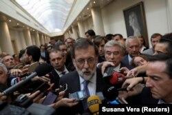 Премьер-министри Мариано Рахой суроолорго жооп берүүдө.