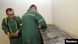 Workers stack gold bars in the safe at the Kumtor goldmine in Kyrgyzstan