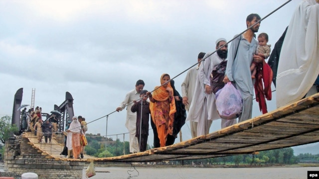 Flood victims cross a temporary bridge as they flee flooded areas of Chakdara, a region in Khyber Pakhtunkhwa Province in early August.