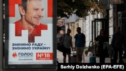People walk past the election advertising of the Holos political party of Svyatoslav Vakarchuk, Ukrainian singer and founder of the Okean Elzy band, in Kyiv.