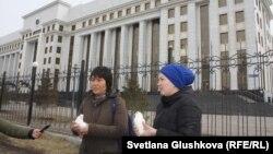 Жительницы Актюбинской области Айнур Жолдыбаева (справа) и Алтынгуль Калижанова перед выпуском голубей у здания генеральной прокуратуры Казахстана. Астана, 31 марта 2017 года.