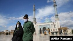 A couple wearing protective face masks following a coronavirus outbreak walk in the Iranian city of Qom.