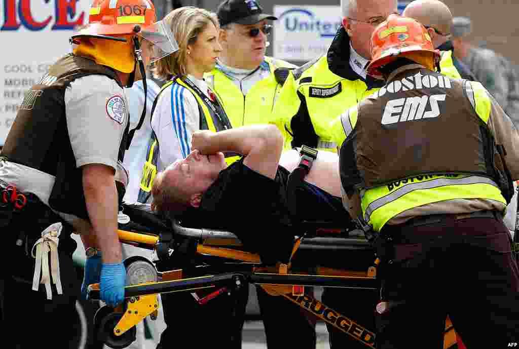 Рятувальники несуть пораненого до машини швидкої допомоги