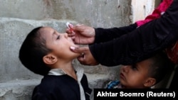 PAKISTAN -- A boy receives polio vaccine drops, during an anti-polio campaign, in a low-income neighbourhood in Karachi, April 9, 2018