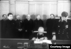 Андрей Вышинский подписывает пакт, своей очереди ждёт Чжоу Эньлай (второй слева). На заднем плане – Сталин и Мао