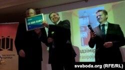 Лешэк Шэрэпка (у цэнтры) уручае грашовую частку прэміі Гедройца Ўладзмеру Някляеву (зьлева)