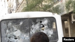 Syrians gather around a bus with shattered windows after shootings during a protest near Damascus. The UN estimates that at least 2,700 people have died in during the unrest in the country.