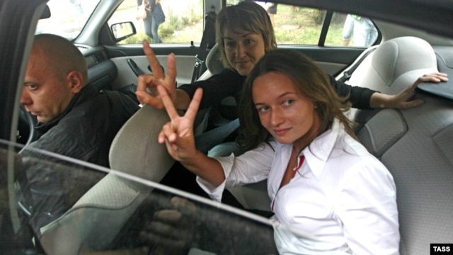 Journalists Irina Kozlik (right) and Yulya Darashkevich show victory signs from a police car after they had been arrested for posing with teddy bears.