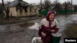 Жінка проходить повз зруйновані будинки. Дебальцеве, 13 березня 2015 року
