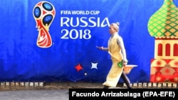 A woman walks past a banner promoting the FIFA World Cup 2018 in Moscow.