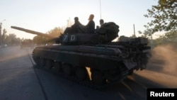 Ukrainian servicemen ride a tank in the southern coastal town of Mariupol on September 5.