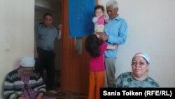 Оралман из Ирана Абдрахман Бабык (с ребенком на руках) вместе со своей семьей в Центре для адаптации оралманов в Актау. 27 мая 2015 года.