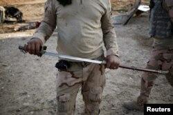 یک سرباز ارتش عراق شمشیری را نشان میدهد که احتمال داده میشود برای بریدن سر توسط نیروهای داعش استفاده میشد