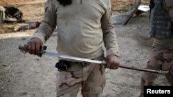 Иракский боец держит в руках саблю, подобную той, что джихадисты используют при обезглавливании пленных