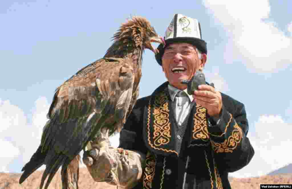پرندهای روزشکار بر دست یک بازدار قرقیزی در لباس سنتی
