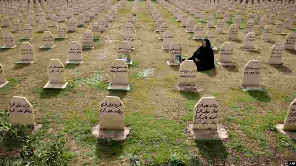 A Kurdish woman visits the grave of her relatives who were killed in a gas attack by former Iraqi leader Saddam Hussein in 1988 on the 24th anniversary of the attack at the memorial site for the victims in the Kurdish town of Halabja. (AFP/Safin Hamed)