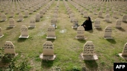 A Kurdish woman visits the graves of her relatives who were killed in the gas attack in 1988 on the 24th anniversary of the attack at the memorial site to the victims in the Iraqi town of Halabja.