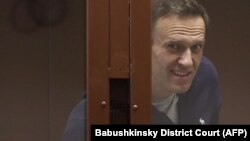 """Aleksei Navalny inside a glass cell during a court hearing in Moscow on February 12. """"We have to all understand that [he] is now not just a political figure for us but a political prisoner who was illegally tried and imprisoned,"""" says Aleksei Shitov, head of Yabloko's youth wing in Novosibirsk."""