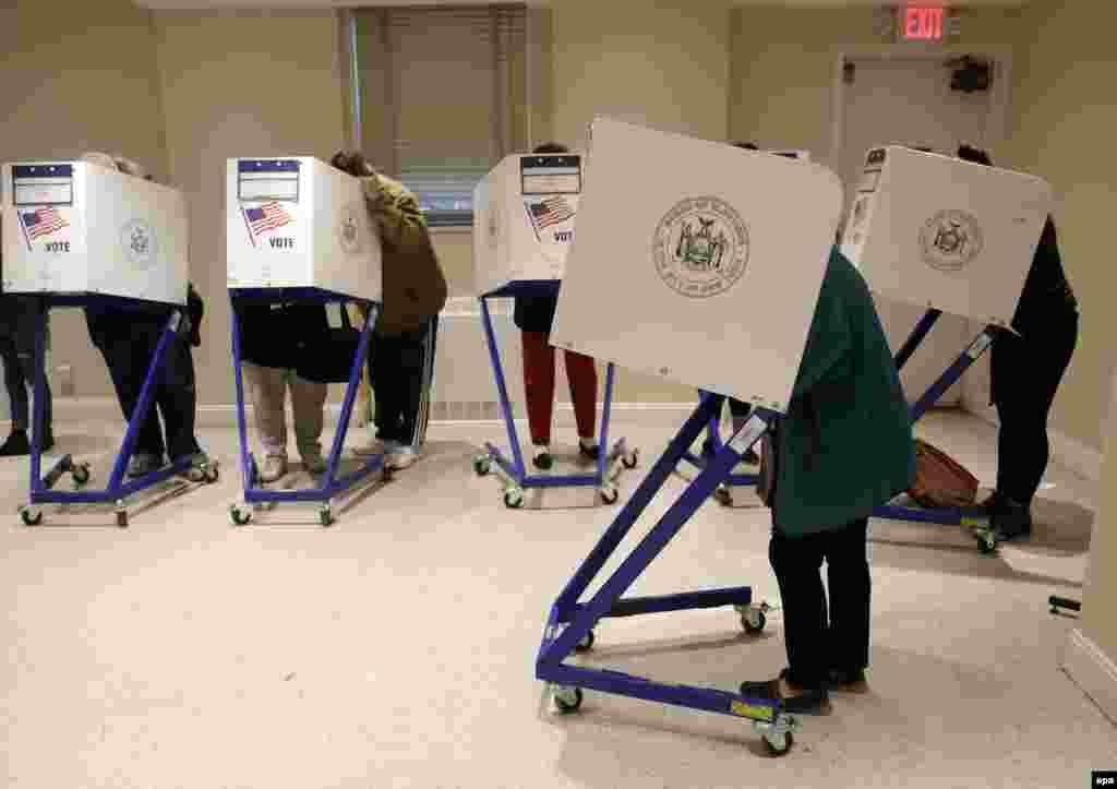 Виборці заповнюють бюлетені в мобільних кабінках для голосування, Нью-Йорк, Манхеттен