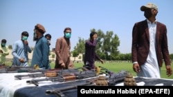 Former Taliban and other militants surrender their weapons during a reconciliation ceremony in Jalalabad on June 25.