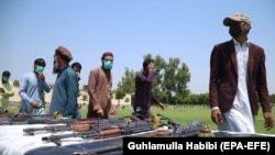 Former militants surrender their weapons during a reconciliation ceremony in Jalalabad on June 25. Many Afghans worry that the impending peace talks will not protect human rights should the hard-line group regain a role in power.