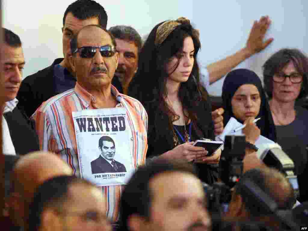 Чоловік із плакатом «розшукується» і фотографією колишнього президента Тунісу Зін аль-Абідіна Бен Алі– один із порисутніх на заочному судовому процесі проти колишнього керівника країни і його дружини, які втекли з Тунісу до Саудівської Аравії після першої революції Арабської весни. Рішенням суду від 20 червня 2011 року Бен Алі був засуджений до 35 років в'язниці і штрафу в 40 мільйонів євро. Через рік Військовий трибунал Тунісу засудив Бен Алі до довічного ув'язнення за вбивство демонстрантів під час придушення повстання в країні. Зовсім незадовго до цього, в 2009 році, Бен Алі набрав на президентських виборах 89,62% голосів виборців.