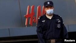 Күзетші Пекиндегі H&M дүкенінің алдында тұр. 9 сәуір 2021 жыл.
