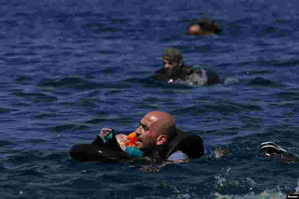 A Syrian refugee holding a baby in a lifetube swims toward shore after their dinghy deflated some 100 meters offshore of the Greek island of Lesbos. (Reuters/Alkis Konstantinidis)