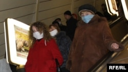 Subway riders in Ukraine wear surgical masks in an effort to protect themselves from swine flu.