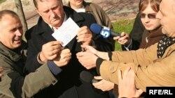 Віктар Канцавенка і Мікола Статкевіч паляць свае пасьведчаньні кандыдатаў у дэпутаты, верасень 2008-га.