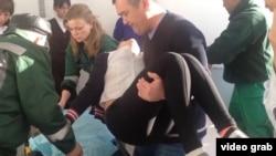 Мужчина несет на руках упавшую в обморок школьницу. Березовка, 21 января 2015 года.