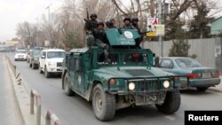 Afghan policeman arrive at the site of a blast and gunfire in Kabul on March 8.