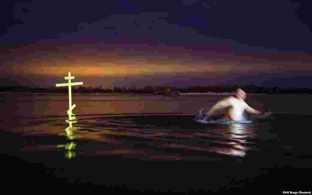 A man walks next to a cross after taking a dip in the shallow water of the Volga River during celebrations of the Orthodox Christian feast of Epiphany in Volgograd, Russia, on January 19. (Reuters/Kirill Braga)