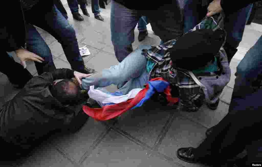 An anti-Russian activist (right) takes away a Russian flag from a pro-Russian activist during a rally in Tbilisi on March 27. (Reuters/David Mdzinarishvili)